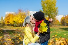 Mother and boy walking in autumn park. The child gently hugs and kisses mom. Mother and little son walking in autumn park. The child gently hugs and kisses mom stock photos