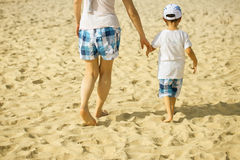 Mother and Boy walking on the beach in sunset Royalty Free Stock Photography
