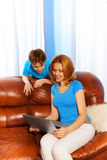 Mother and boy watching at laptop screen on sofa Royalty Free Stock Photography