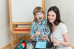 Mother with boys son paint colors at home Stock Photo