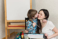 Mother with boys son paint colors at home Stock Photography