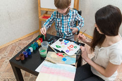 Mother with boys son paint colors at home Stock Photos
