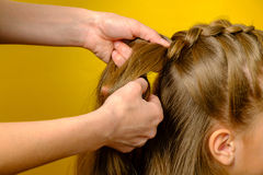 Mother braiding French braid her daughter Stock Image