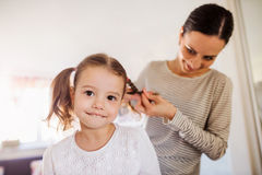 Mother braiding hair of her daughter in the morning. Beautiful young mother braiding hair of her little daughter in the morning Stock Photo
