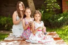 Mother braiding hair to two daughters on grass at park Royalty Free Stock Photography