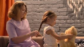 Mother braiding her little daughter`s hair, parent and kid sitting together on sofa, family concept indoors stock video