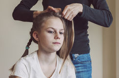 Mother braiding young girls hair. Real life portrait picture of caucasian teen girl with deliberate warm mate filter Stock Image