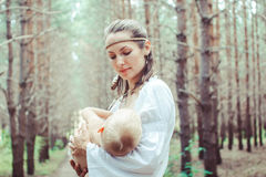 Mother breast-feeding a baby in nature Stock Photo