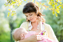 Mother breast feeding baby outdoors. Young mother breast feeding her baby girl outdoors Stock Image