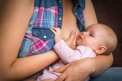 Mother breast feeding newborn baby at home Stock Image
