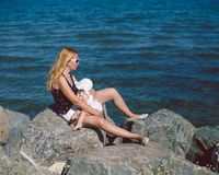 Mother breastfeeding baby girl on the beach. Seashore during a s Stock Photo