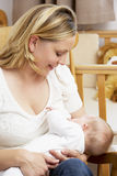 Mother Breastfeeding Baby In Nursery Stock Photo