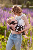 Mother breastfeeding her baby in a field of purple flowers. Horisontal shot Stock Photos
