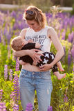 Mother breastfeeding her baby in a field of purple flowers. Horisontal shot Royalty Free Stock Photography