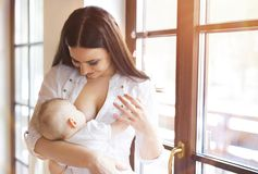 Mother breastfeeding her baby. Mother breastfeeding her little baby girl in her arms stock photography