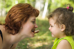 Mother breastfeeding her child. Young woman feeding her child, comic situation Royalty Free Stock Photos