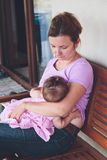 Mother breastfeeding her little baby on the patio Stock Photography