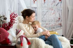 Mother breastfeeding her toddler son sitting in cozy armchair, wintertime stock images
