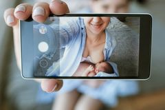 Mother breastfeeding mobile photo newborn baby Stock Images