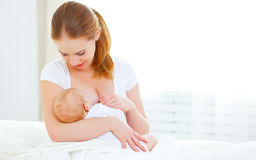 Mother breastfeeding newborn baby in white bed Royalty Free Stock Image