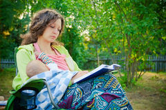 Mother breastfeeding while reading the book. Mother breastfeeding her baby, seating on a chair outside and reading the book stock photography