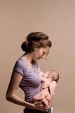 Mother breastfeeds her baby Stock Photos