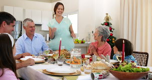 Mother bringing turkey to dinner table for christmas Royalty Free Stock Photo