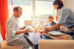 Mother brings a dish of meal at table to her hungry family Royalty Free Stock Photos