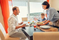 Mother brings a dish of meal at table to her hungry family Royalty Free Stock Image