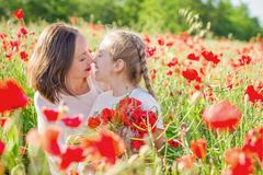 Mother brunette in white with daughter together on blossoming red poppies field Royalty Free Stock Image