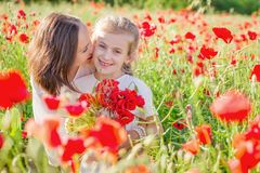 Mother brunette in white with daughter together on blossoming red poppies field Stock Photography