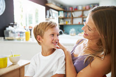 Mother Brushes Son's Hair As He Plays With Digital Tablet Stock Photo