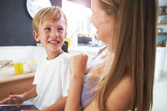 Mother Brushes Son's Hair As He Plays With Digital Tablet Royalty Free Stock Photos