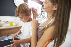 Mother Brushes Son's Hair As He Plays With Digital Tablet Royalty Free Stock Images