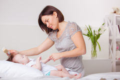 Mother brushing baby  hair Royalty Free Stock Images
