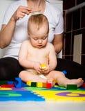 Mother brushing baby's hair royalty free stock image