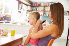 Mother Brushing Daughter's Hair At Breakfast Table Royalty Free Stock Images