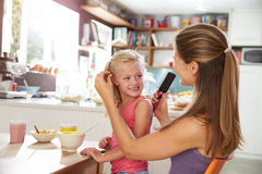 Mother Brushing Daughter's Hair At Breakfast Table Royalty Free Stock Photography