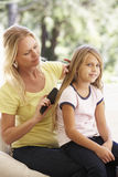 Mother Brushing Daughters Hair On Sofa At Home Stock Photos