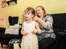 Mother brushing her daughter. Girl in a beautiful dress is going to birthday. stock photo