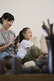 Mother brushing her daughters hair Royalty Free Stock Photo