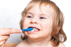 Mother brushing teeth baby boy kid 2 years stock photography
