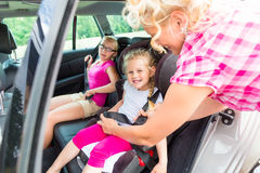 Mother buckling up on child in car Stock Image