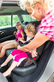 Mother buckling up on child in car Royalty Free Stock Images