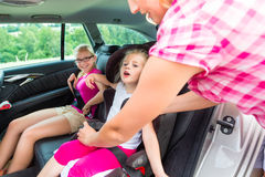 Mother buckling up on child - car safety seat Royalty Free Stock Images