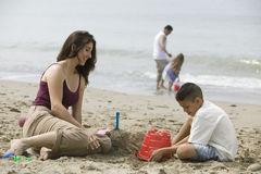 Mother building sandcastles with son on beach Royalty Free Stock Images