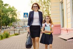 Mother businesswoman takes the child to school. Urban style background Stock Photography