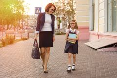 Mother businesswoman takes the child to school. Urban background Royalty Free Stock Images