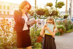 Mother businesswoman takes the child to school. Urban background Royalty Free Stock Photo