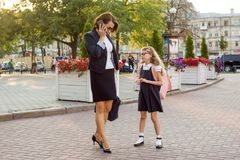 Mother businesswoman takes the child to school. Urban background Stock Image
